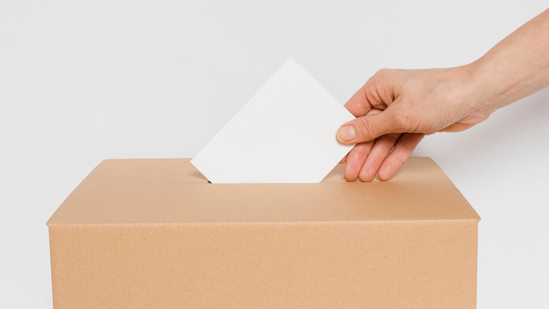 Mano introduciendo papeleta electoral en una urna